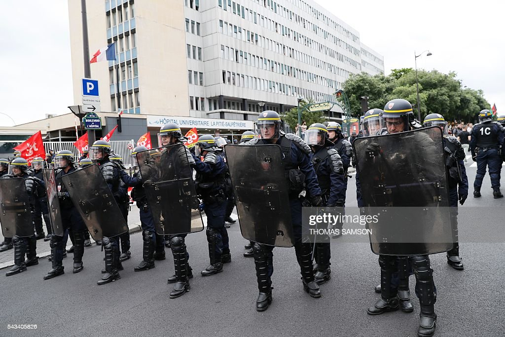 French anti-riot police officers stand in a street during a demonstration against controversial labour reforms, on June 28, 2016 in Paris. Unions have called repeated strikes and marches in opposition to the law, which seeks to bring down France's intractable 10-percent unemployment rate by making it easier to hire and fire workers. / AFP / Thomas SAMSON