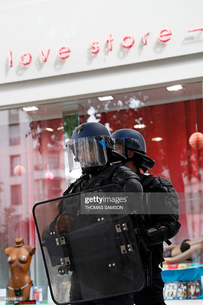 French anti-riot police officers stand in front of a shop during a demonstration against controversial labour reforms, on June 28, 2016 in Paris. Unions have called repeated strikes and marches in opposition to the law, which seeks to bring down France's intractable 10-percent unemployment rate by making it easier to hire and fire workers. / AFP / Thomas SAMSON