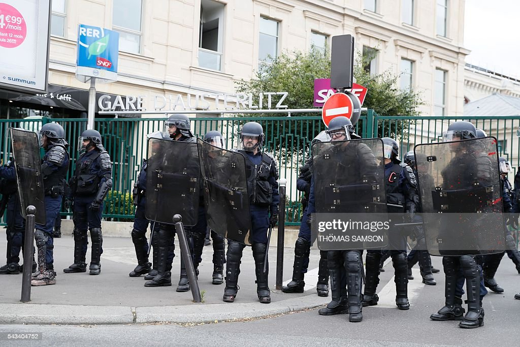 French anti-riot police officers stand in front of the Austerlitz train station during a demonstration against controversial labour reforms, on June 28, 2016 in Paris. Unions have called repeated strikes and marches in opposition to the law, which seeks to bring down France's intractable 10-percent unemployment rate by making it easier to hire and fire workers. / AFP / Thomas SAMSON