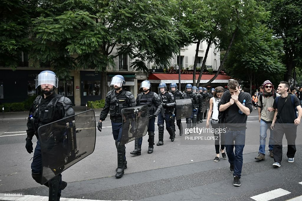 French anti-riot police officers walk during a demonstration against controversial labour reforms, on June 28, 2016 in Paris. Unions have called repeated strikes and marches in opposition to the law, which seeks to bring down France's intractable 10-percent unemployment rate by making it easier to hire and fire workers. / AFP / PHILIPPE
