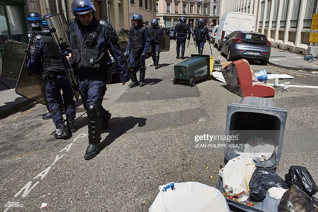 French anti-riot police officers walk past garbage bins thrown accross sidewalks during a demonstration against controversial labour reforms, on June 28, 2016 in Lyon. Unions have called repeated strikes and marches in opposition to the law, which seeks to bring down France's intractable 10-percent unemployment rate by making it easier to hire and fire workers. / AFP / JEAN