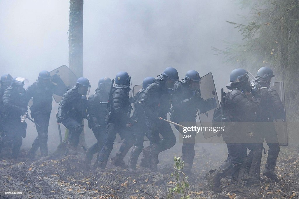 French anti-riot police officers walk through smoke from tear gas, on November 24, 2012 in Notre-Dame-des-Landes as they seek to evict squatters from protected swampland where Prime Minister Jean-Marc Ayrault wants to build a new airport. Clashes between police and protesters resumed at Notre-Dame-des-Landes, outside the western city of Nantes, as officers fired tear gas and squatters threw stones and glass bottles at them in return. AFP PHOTO / JEAN-SEBASTIEN EVRARD