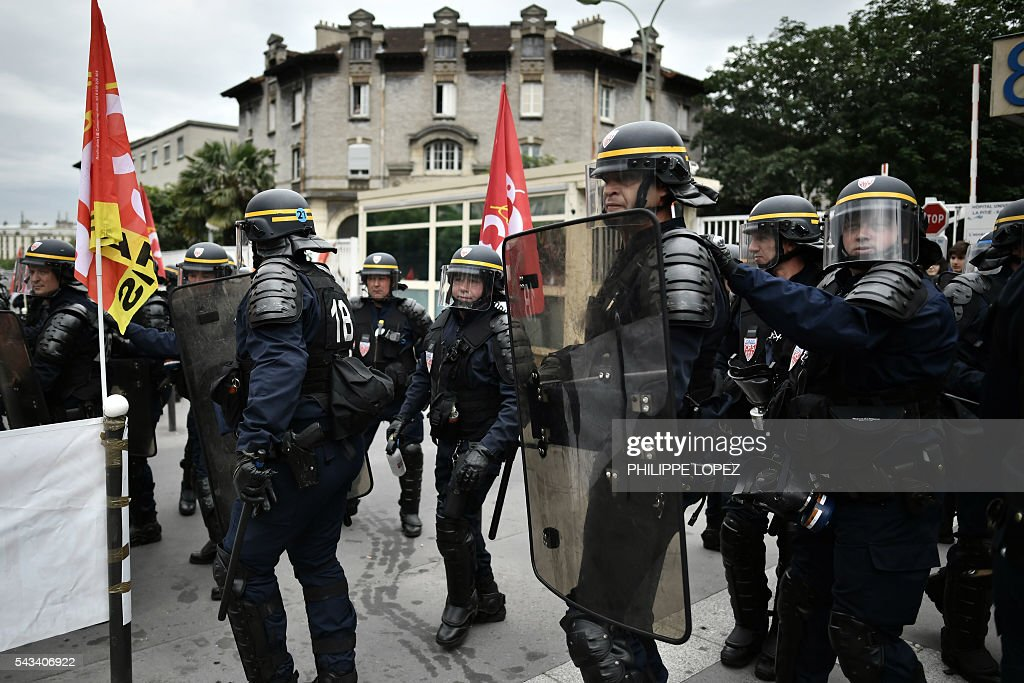 French anti-riot police stand during a demonstration against controversial labour reforms, on June 28, 2016 in Paris. Unions have called repeated strikes and marches in opposition to the law, which seeks to bring down France's intractable 10-percent unemployment rate by making it easier to hire and fire workers. / AFP / PHILIPPE