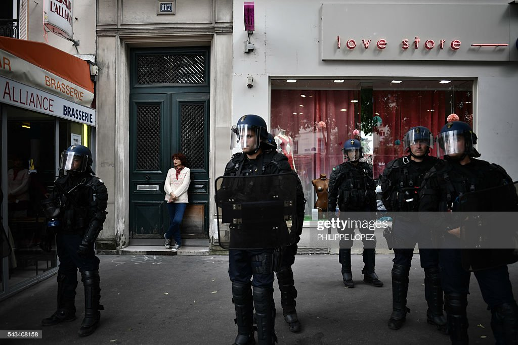 French anti-riot police stand in front of shops during a demonstration against controversial labour reforms, on June 28, 2016 in Paris. Unions have called repeated strikes and marches in opposition to the law, which seeks to bring down France's intractable 10-percent unemployment rate by making it easier to hire and fire workers. / AFP / PHILIPPE