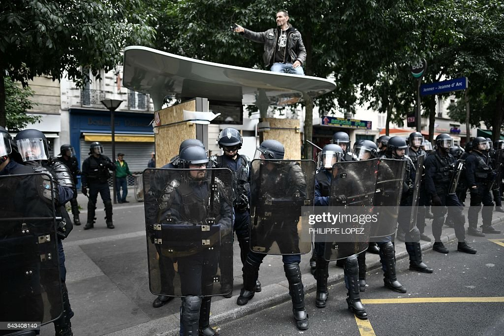 French anti-riot police stand in line in a street as a man sits atop a roof during a demonstration against controversial labour reforms, on June 28, 2016 in Paris. Unions have called repeated strikes and marches in opposition to the law, which seeks to bring down France's intractable 10-percent unemployment rate by making it easier to hire and fire workers. / AFP / PHILIPPE