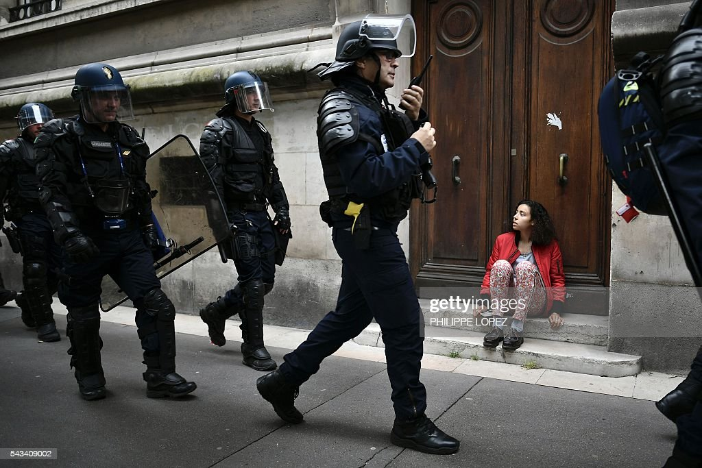 French anti-riot police walks as a woman sits in a street during a demonstration against controversial labour reforms, on June 28, 2016 in Paris. Thousands of people took to the streets of Paris today in the latest protest march in a marathon campaign against the French Socialist government's job market reforms. / AFP / PHILIPPE