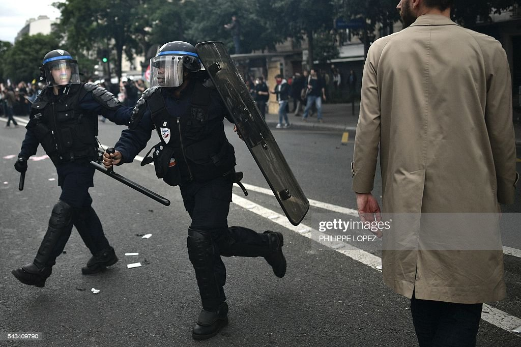 A French anti-riot policeman runs as a man walks by during a demonstration against controversial labour reforms, on June 28, 2016 in Paris. Thousands of people took to the streets of Paris today in the latest protest march in a marathon campaign against the French Socialist government's job market reforms. / AFP / PHILIPPE