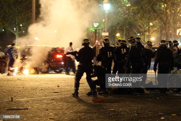 French antiriot policemen face supporters of the Algerian national football team while a motorcycle is burning on the ChampsElysees avenue in Paris...
