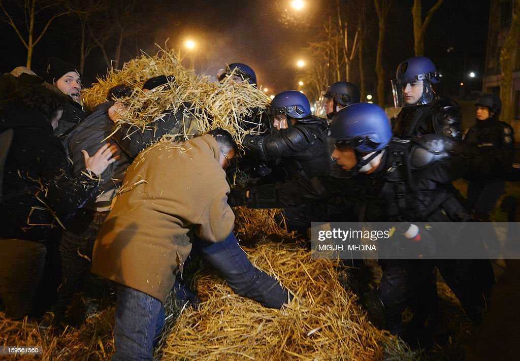 French antiriot policemen try to evacuate farmers who spread straw on the pavement early on January 16, 2013 in Paris, near the Agriculture ministry and the Prime Minister official residence, the Hotel Matignon, during a protest called by farmers union FNSEA against new constraints arising from the applications of European Union rules against nitrates. A new map identifies 'vulnerable areas' to nitrates which require special protection to not pollute water resources. AFP PHOTO MIGUEL MEDINA