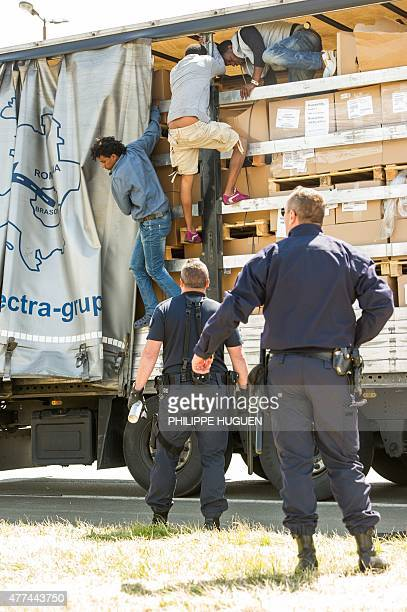 French antirot police evacuate migrants trying to hide in trucks heading for England in the French northern harbour of Calais on June 17 2015 AFP...