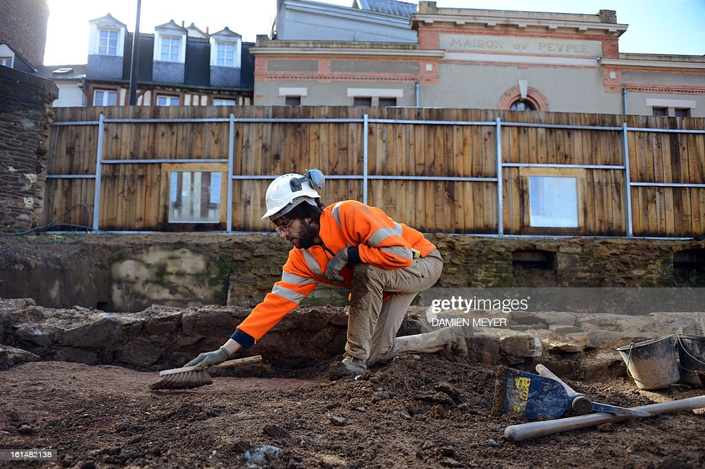 A French archaelogist of Inrap (Institut national de recherches archeologiques preventives) digs a 8,000 SQM area on the site of a former convent on February 11, 2013 in the city center of Rennes, western France. The remains of a Gallo-Roman temple and 550 medieval and modern burials, including several lead sarcophagus, were unearthed during archaeological excavations on the site of the future Palais des Congres (Congress Center). AFP PHOTO / DAMIEN MEYER
