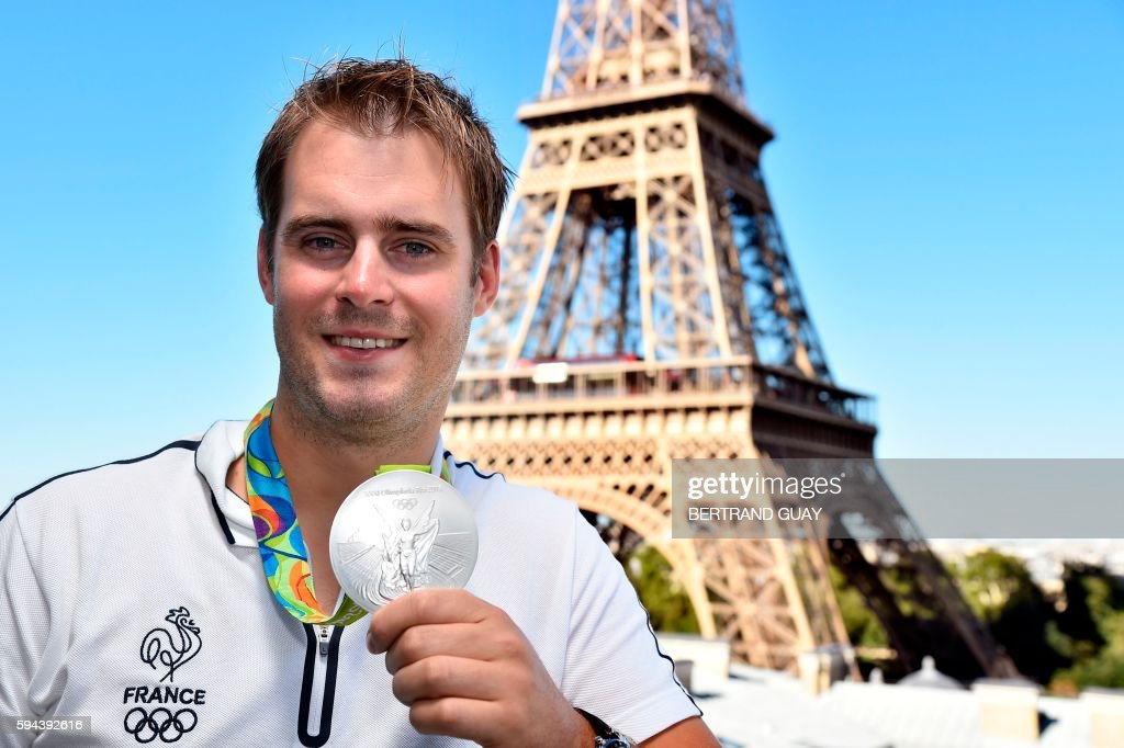 French archer JeanCharles Valladont poses with his silver medal on August 23 in front of the Eiffel tower in Paris France's Olympic team landed in...