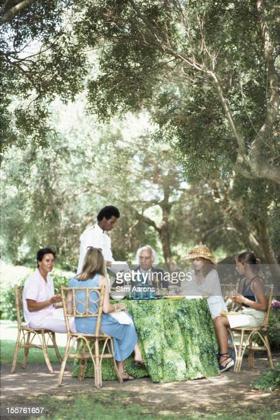 French architect Jacques Couelle and fellow diners being served lunch in the grounds of Couelle's home on the Costa Smeralda Sardinia Italy 1978