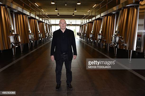 French architect Jean Nouvel poses in front of tanks of the Chateau La Dominique on June 2 2014 in SaintEmillion southwestern france Nouvel...