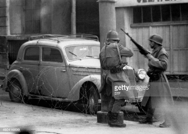 French armed soldiers are on watch round a corner in BabElOued 22 March 1962 four days after the Evian agreement Des soldats de l'armée française...