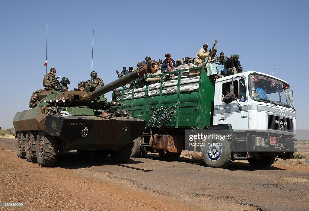 A French armoured vehicule overtakes a local truck as the convoy of French army vehicules head toward Gao on February 7, 2013 on the road from Gossi. Four Malian civilians were killed by a landmine in territory reclaimed from Islamist rebels, police said as France mulled handing over its four-week-old intervention to UN peacekeepers.