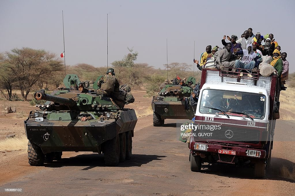 French armoured vehicules overtake a local truck as the convoy of French army vehicules head toward Gao on February 7, 2013 on the road from Gossi. Four Malian civilians were killed by a landmine in territory reclaimed from Islamist rebels, police said as France mulled handing over its four-week-old intervention to UN peacekeepers. AFP PHOTO / PASCAL GUYOT