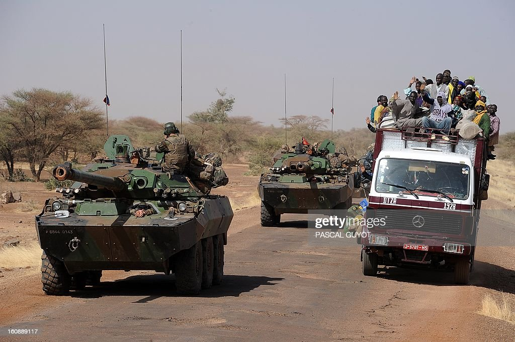 French armoured vehicules overtake a local truck as the convoy of French army vehicules head toward Gao on February 7, 2013 on the road from Gossi. Four Malian civilians were killed by a landmine in territory reclaimed from Islamist rebels, police said as France mulled handing over its four-week-old intervention to UN peacekeepers.
