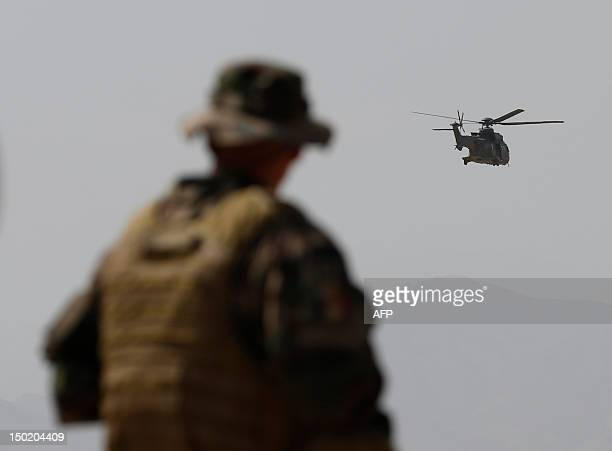 A French Army mentor looks on as a Eurocopter AS 532 Cougar helicopter of the French Helicopter Battalion 'Mousquetaire' flies as soldiers of the...