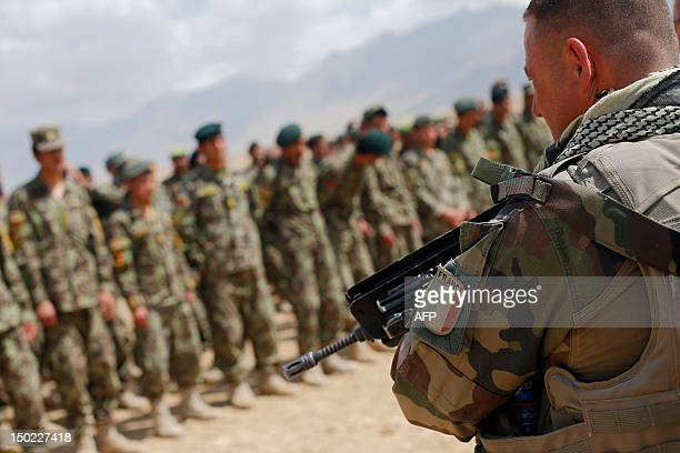 A French Army mentor member of the 'Epidote' unit stands guard as soldiers from the Afghan National Army listen after watching training exercises and...