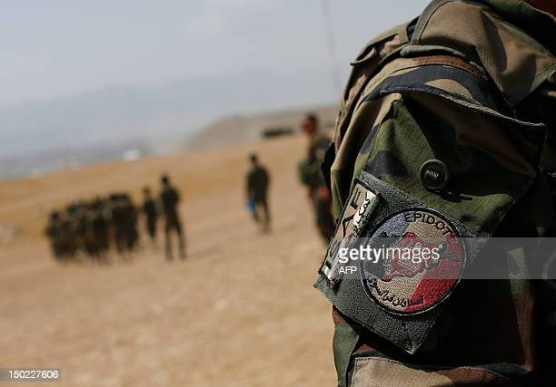 A French Army mentor with a patch of the 'Epidote' unit watches as soldiers from the Afghan National Army listen after watching training exercises...