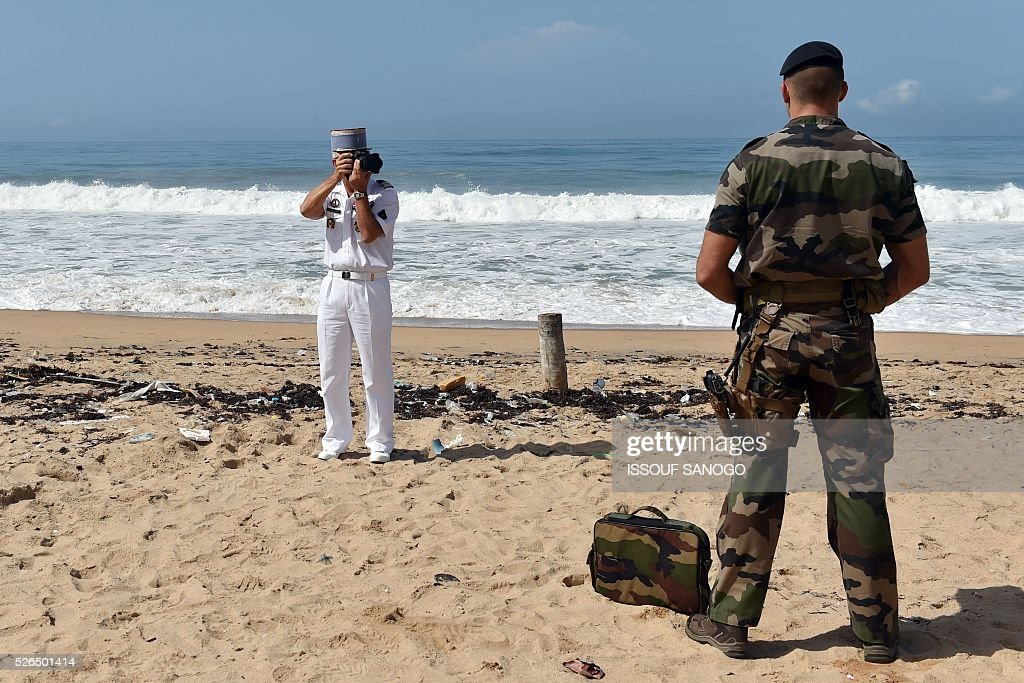 French army officer takes a picture of a soldier posing on the beach as they wait, on April 30, 2016, for the arrival of French Defence Minister Jean-Yves Le Drian at the Grand-Bassam beach by the Hotel Etoile du Sud to pay a tribute to the 19 victims of the jihadist attack of March 13. France will increase the number of its troops in Ivory Coast, Defence Minister Jean-Yves Le Drian said on April 29 on a trip to the African nation which hosts a regional base for French forces. / AFP / ISSOUF