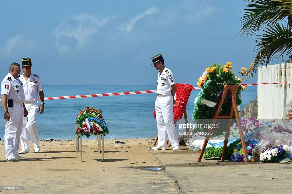 French army officers look at sprays of flowers as they wait, on April 30, 2016, for the arrival of French Defence Minister Jean-Yves Le Drian at the Grand-Bassam beach by the Hotel Etoile du Sud to pay a tribute to the 19 victims of the jihadist attack of March 13. France will increase the number of its troops in Ivory Coast, Defence Minister Jean-Yves Le Drian said on April 29 on a trip to the African nation which hosts a regional base for French forces. / AFP / ISSOUF