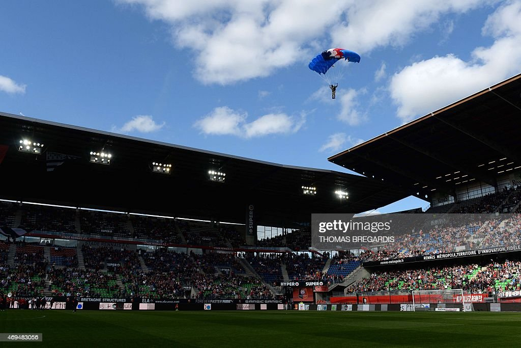 French army Parachutist is ready to land on the field with the ball before the French L1 football match between Rennes and Guingamp on April 12, 2015 at the route de Lorient stadium in Rennes, western France.
