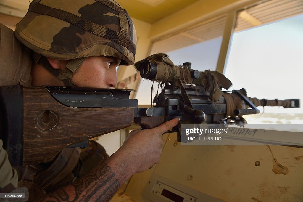 A French Army sniper watches on January 30, 2013 with his FR 12/7 PGM rifle the area around Timbuktu airport two days after French-led forces recaptured the northern Malian desert city. French troops on January 30 entered Kidal, the last Islamist bastion in Mali's north after a whirlwind Paris-led offensive, as France urged peace talks to douse ethnic tensions targeting Arabs and Tuaregs. AFP PHOTO / ERIC FEFERBERG