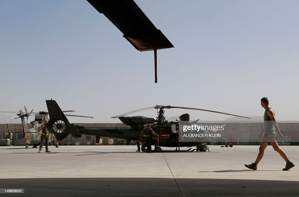 A French army soldier of the 1st Combat Helicopter Regiment (1er Regiment d'Helicopteres de Combat) walks by an Aerospatiale Gazelle Viviane helicopter at the French Helicopter Battalion 'Mousquetaire' at the Kabul International airport, in Kabul, on August 3, 2012. France is the fifth largest contributor to NATO's International Security Assistance Force (ISAF), which is due to pull out the vast majority of its 130,000 troops by the end of 2014.