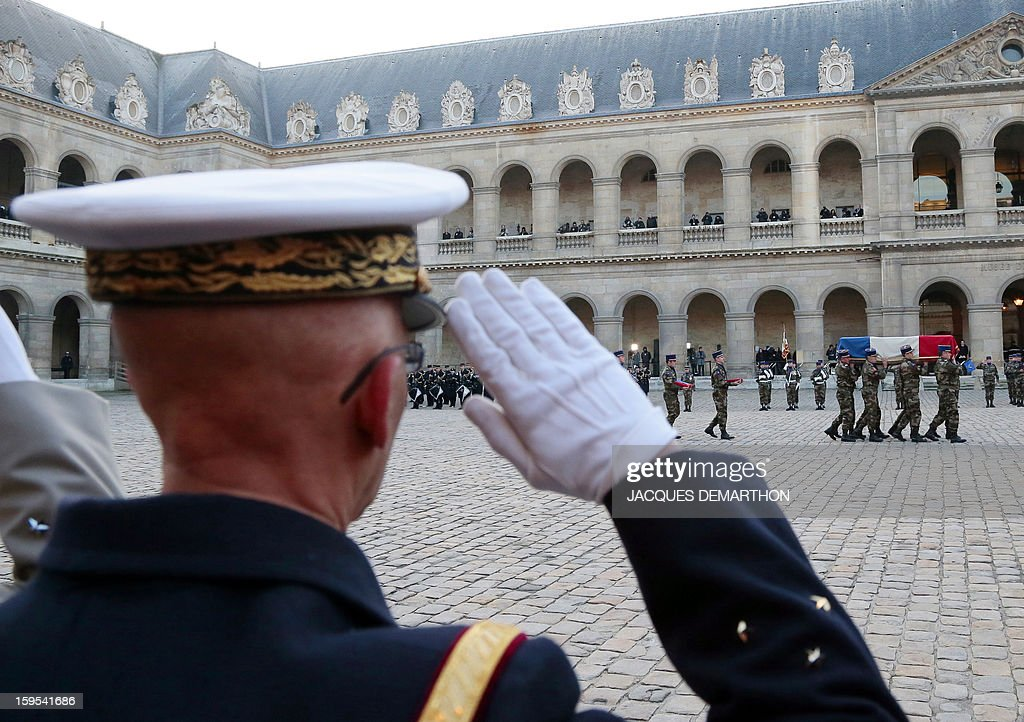 A French army soldier pays respect while French army soldiers are carrying the coffin of French air force lieutenant Damien Boiteux during a funeral service at the Invalides courtyard in Paris, on January 15, 2013. French pilot Damien Boiteux was killed on January 11 during a helicopter raid launched to support Mali ground troops in the battle for the key town of Kona, and to prevent Islamist groups controlling northern Mali from advancing toward the capital Bamako. AFP PHOTO / POOL / JACQUES DEMARTHON