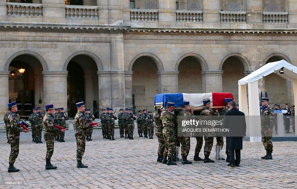 French army soldiers carry the coffin of French air force lieutenant Damien Boiteux during a funeral service at the Invalides courtyard in Paris, on January 15, 2013. French pilot Damien Boiteux was killed on January 11 during a helicopter raid launched to support Mali ground troops in the battle for the key town of Kona, and to prevent Islamist groups controlling northern Mali from advancing toward the capital Bamako. AFP PHOTO / POOL / JACQUES DEMARTHON