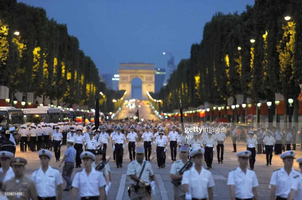 French armymen parade at dawn on the Champs Elysees in Paris on July 12 during the rehearsal of the French national celebration the Bastille Day...