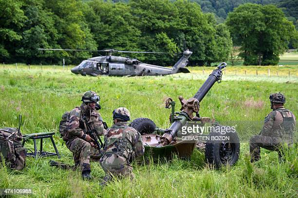 French artillery kneel beside a 120mm mortar near a US Blackhawk helicopter during a FrenchUS 'Royal Blackhawk' military exercise with French US...