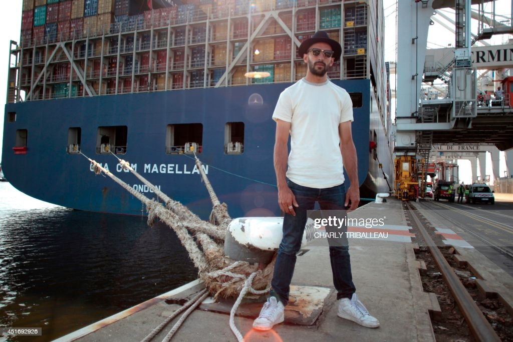 French artist and photographer JR is pictured near the CMA-CGM Magellan cargo ship on July 4, 2014 in Le Havre, northwestern France. A cargo boat displaying on its right flank a 5,000 m2 photo of the eyes of an African woman is leaving Le Havre on July 4 towards Malaysia. This gigantic collage is the new challenge of photographer JR, a specialist of artistic challenges. AFP PHOTO / CHARLY TRIBALLEAU.
