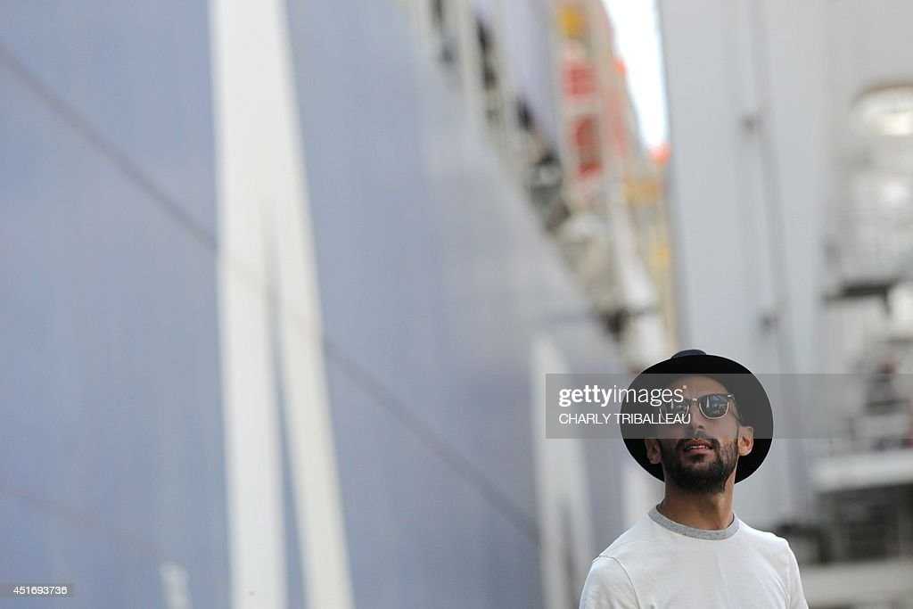 French artist and photographer JR is pictured near the CMA-CGM Magellan cargo ship on July 4, 2014 in Le Havre, northwestern France. A cargo boat displaying on its right flank a 5,000 m2 photo of the eyes of an African woman is leaving Le Havre on July 4 towards Malaysia. This gigantic collage is the new challenge of photographer JR, a specialist of artistic challenges.