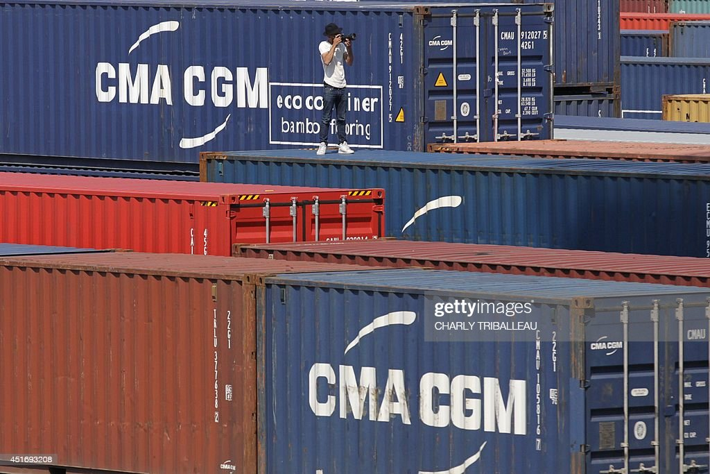French artist and photographer JR is pictured onto the CMA-CGM Magellan cargo ship on July 4, 2014 in Le Havre, northwestern France. A cargo boat displaying on its right flank a 5,000 m2 photo of the eyes of an African woman is leaving Le Havre on July 4 towards Malaysia. This gigantic collage is the new challenge of photographer JR, a specialist of artistic challenges. AFP PHOTO / CHARLY TRIBALLEAU.