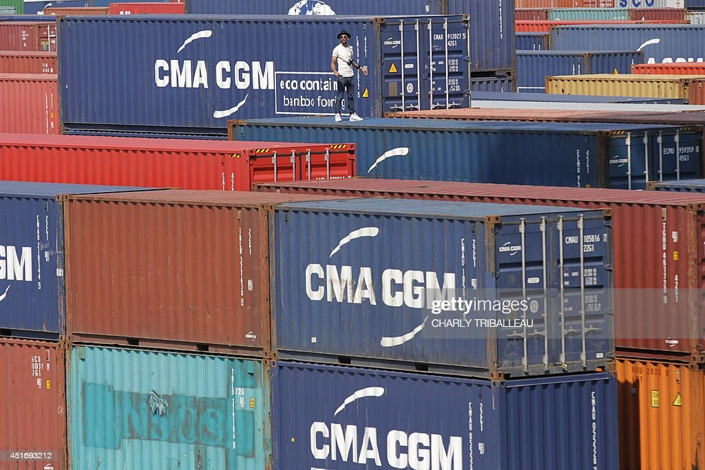 French artist and photographer JR is pictured onto the CMA-CGM Magellan cargo ship on July 4, 2014 in Le Havre, northwestern France. A cargo boat displaying on its right flank a 5,000 m2 photo of the eyes of an African woman is leaving Le Havre on July 4 towards Malaysia. This gigantic collage is the new challenge of photographer JR, a specialist of artistic challenges.