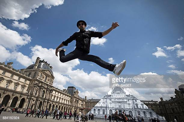TOPSHOT French artist and photographer JR jumps in front the Louvre pyramid after recovering it 'with a surprising anamorphic image' according to the...