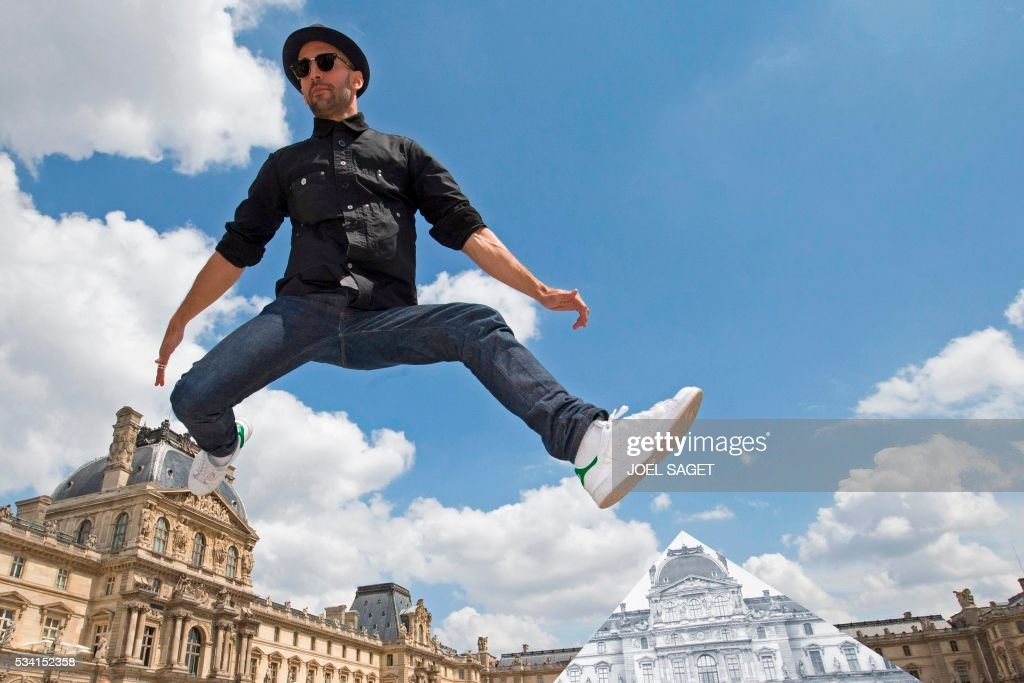 French artist and photographer JR jumps in front the Louvre pyramid after recovering it 'with a surprising anamorphic image', according to the museum in Paris on May 25, 2016. This recovering introduces the opening of JR exhibition 'Contemporary art JR at the Louvre' will run from May 25 to June 27, 2016. SAGET