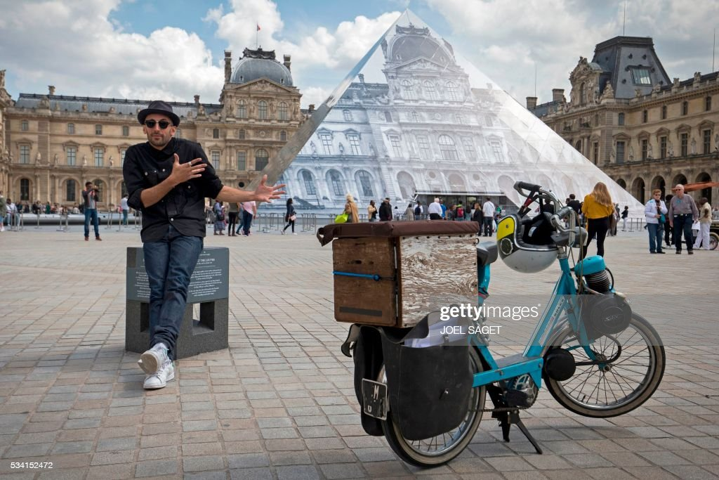 French artist and photographer JR poses in front the Louvre pyramid after recovering it 'with a surprising anamorphic image', according to the museum in Paris on May 25, 2016. This recovering introduces the opening of JR exhibition 'Contemporary art JR at the Louvre' will run from May 25 to June 27, 2016. SAGET
