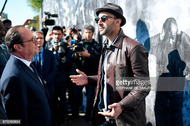 French artist and photographer JR talks with French President Francois Hollande during the inauguration of JR's fresco of the inhabitants of the...
