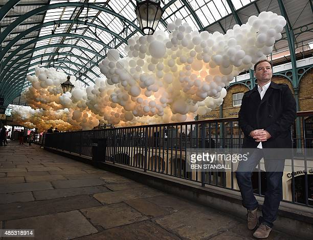 French artist Charles Petillon poses for pictures with his artwork made of balloons entitled 'Heartbeat' in London's Covent Garden Market building on...