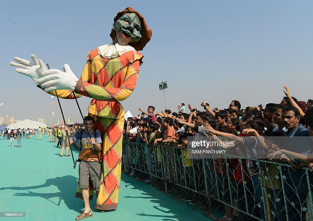 A French artist entertains Indian audience members with his puppet during the 25th International Kite Festival 2013 in Ahmedabad on January 13, 2013. The first edition of this festival was held in 1989 and was attended by Sir Edmund Hillary, legendary mountaineer and the first person to scale Mt. Everest. AFP PHOTO/ Sam PANTHAKY