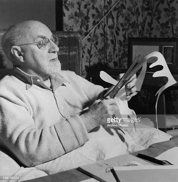 French artist Henri Matisse making paper cutouts in bed at his home in Vence France circa 1947