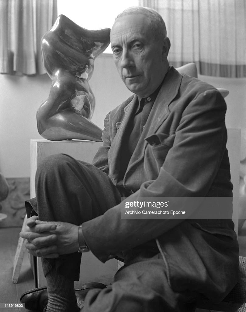 French artist Jean Arp, sitting to the floor in front of a sculpture of his, full-figured portrayed, wearing a corduroy blazer, Paris, 1948.