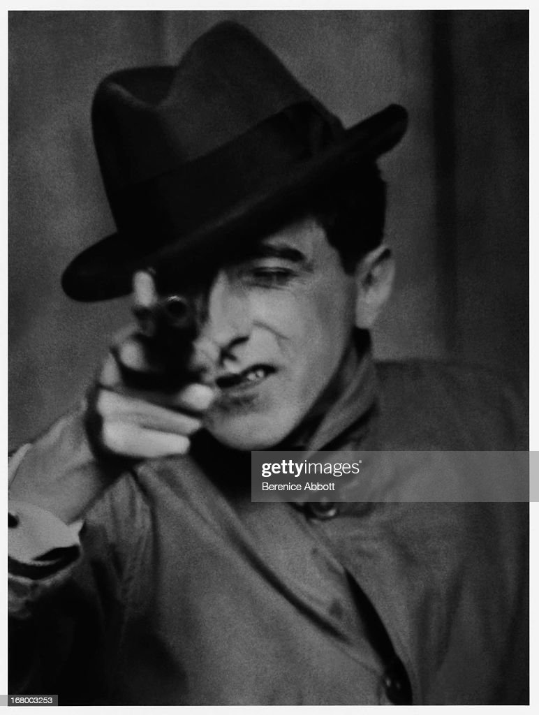 French artist, poet, filmmaker and writer <a gi-track='captionPersonalityLinkClicked' href=/galleries/search?phrase=Jean+Cocteau&family=editorial&specificpeople=211437 ng-click='$event.stopPropagation()'>Jean Cocteau</a> (1889 - 1963) posing as a gangster with a gun, 1926.