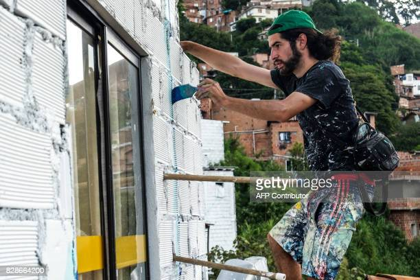 French artist Tarik Bouanani paints a wall at El Pesebre shantytown in the outskirts of Medellin Colombia on June 29 2017 Bouanani turned 230 brick...