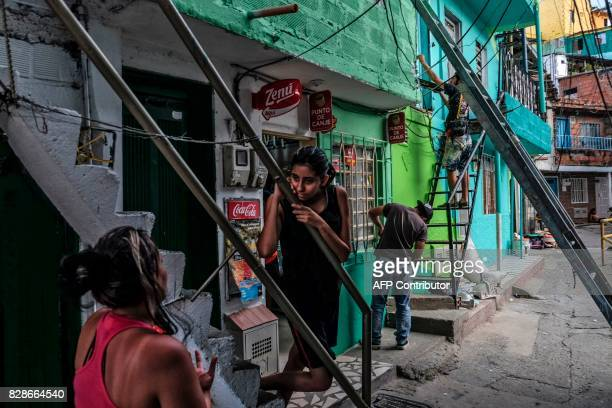 French artist Tarik Bouanani paints a wall next to residents at El Pesebre shantytown in the outskirts of Medellin Colombia on June 29 2017 Bouanani...