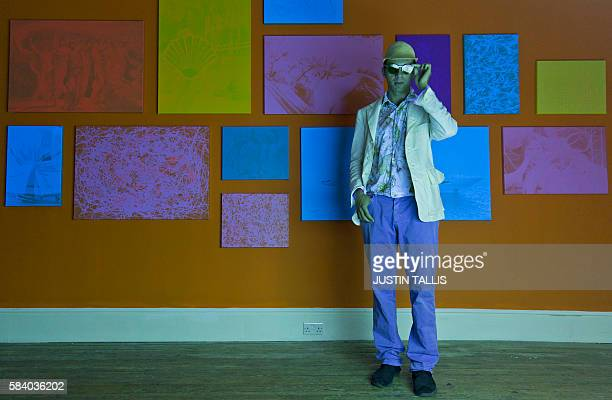 French artist Zevs poses for a photograph alongside a series of pictures that are only visible under ultraviolet light during an event to promote his...